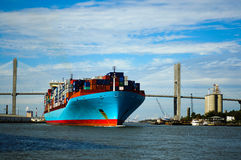 Cargo ship sailing under the bridge Stock Photo
