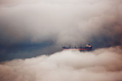 Cargo ship sailing in water of clouds Stock Photos