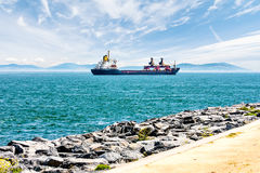 Cargo ship sails on a background of blue mountains Royalty Free Stock Images