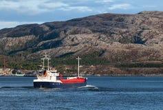Cargo ship sails on Norwegian fjord Stock Photos