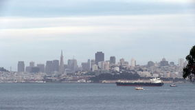 Cargo Ship In San Francisco Bay With City Behind. Ship Ferry And Tugboat In San Francisco Bay Moving In Front Of City stock footage