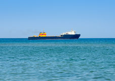 Cargo ship in the sea against the blue sky Royalty Free Stock Photo