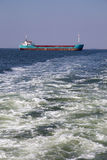 Cargo ship on the sea with waves foreground. And blue clear sky background Stock Photography