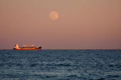 Full Moon Shines On Anchored Cargo Ship Royalty Free Stock Photography