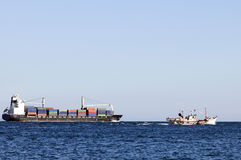 Cargo Ship and Small Trawler Boat Departing Royalty Free Stock Photos