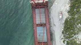 Cargo ship standing at shoal of sand beach after run aground