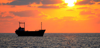 Cargo ship and sunset. Royalty Free Stock Photography