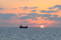 Cargo ship and sunset. Royalty Free Stock Photos