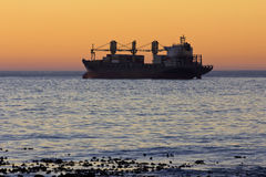 Cargo ship at sunset  Royalty Free Stock Photos