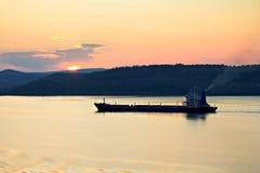 Cargo ship at sunset Stock Photo