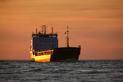 Cargo ship and the sunset Royalty Free Stock Photos