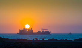 Cargo ship at sunset Stock Photo