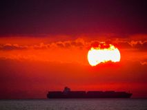 Cargo ship at sunset Stock Images