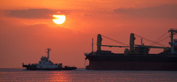 Cargo ship and  sunset at the ocean Stock Images