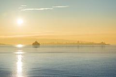 Cargo ship at sunset in the sea Stock Photos