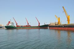 Cargo ship with tower cranes stock images