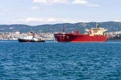 Cargo ship and tug boat Stock Photography