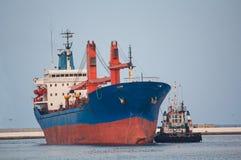 Cargo ship and tug boat Stock Photos