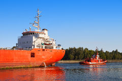 Cargo ship with tug boat Stock Photography