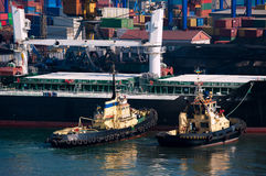 Cargo ship and tug boat in port Stock Photo