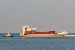 Cargo ship and tug call at the port Stock Photo