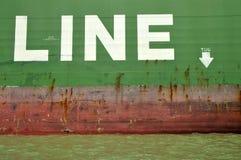Cargo Ship Tug Line. Rusting Hull of International Cargo Ship at dock Royalty Free Stock Photo