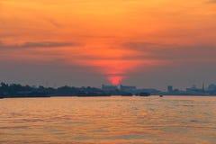 Cargo ship on river at sunrise. Cargo ship and tugboat sailing on Chao Phraya river at sunrise with twilight sky, Bangkok, Thailand Stock Image