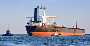 Cargo ship and two tugboats. Royalty Free Stock Photos