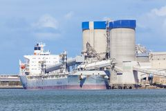 Cargo ship unloading at a cement plant Royalty Free Stock Photos