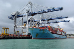 Cargo ship unloading containers in Ports of Auckland New Zealand. AUCKLAND,  NZL - OCT 13 2015:Big cargo ship unloading containers in Ports of Auckland New Royalty Free Stock Images