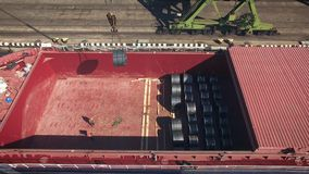 Cargo ship unloading in port. Aerial view of cargo ship unloading in port stock footage