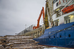 Cargo ship unloading timber Royalty Free Stock Photos