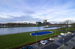 Cargo ship in water dutch river next to the stadium and car parking lot. Early Saturday morning view through the window with a bright blue sky Royalty Free Stock Images