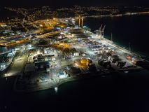Aerial, Shipping Container Depot At Night. Cargo shipping bay, stacking crates and cranes with city roads in the background Royalty Free Stock Images