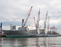 Cargo Shipping. Photo of a docked cargo ship waiting for the cranes to load the containers Stock Photo
