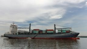 the cargo shipping vessel and  the  custom department 's officers small boat Royalty Free Stock Images