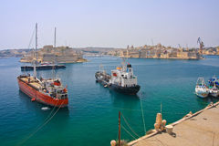 Cargo ships. Two big ships waiting in port of Valetta. Luxury sailing yacht in background Royalty Free Stock Image