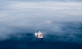 Cargo ships emerging from fog. Stock Photography