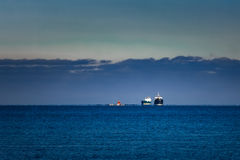Cargo ships far in still water Royalty Free Stock Images