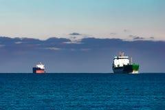 Cargo ships far in still water Stock Photo