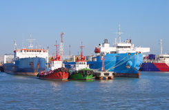 Cargo ships and guard boats docked in port Royalty Free Stock Images