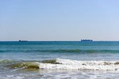 Cargo ships on ocean horizon stock photos