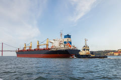 Cargo ships in river being tugged Stock Photography