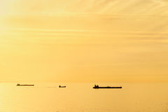 Cargo ships at sunset with calm sea Royalty Free Stock Photo