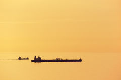 Cargo ships at sunset with calm sea Royalty Free Stock Photos