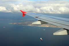 Cargo ships under wing of flying plane Stock Photography