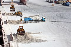 Cargo terminal for loading of gypsum cargo by ship cranes to bulk carrier. Port of Salalah, Oman. Cargo terminal for loading of gypsum cargo to bulk carrier by royalty free stock image