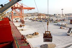 Cargo terminal for loading of gypsum cargo by ship cranes to bulk carrier. Port of Salalah, Oman. Cargo terminal for loading of gypsum cargo to bulk carrier by stock image