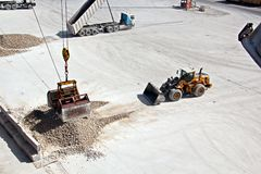 Cargo terminal for loading of gypsum cargo by ship cranes to bulk carrier. Port of Salalah, Oman. Cargo terminal for loading of gypsum cargo to bulk carrier by stock images