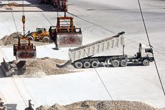 Cargo terminal for loading of gypsum cargo by ship cranes to bulk carrier. Port of Salalah, Oman. Cargo terminal for loading of gypsum cargo to bulk carrier by stock photography